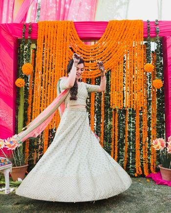 twirling bride with mehendi backdrop made of genda phool