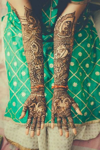 Traditional bridal mehendi design with wedding portraits