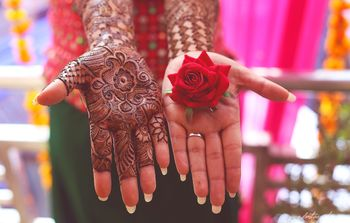 Mehendi on one hand rose on other