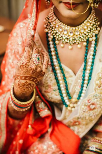 Bride wearing green jewellery and cocktail ring