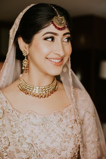 A happy bridal shot in a beautiful pastel lehenga and subtle makeup.
