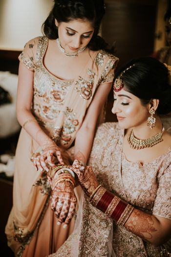 Bride with sister on her wedding in light lehengas and subtle makeup.