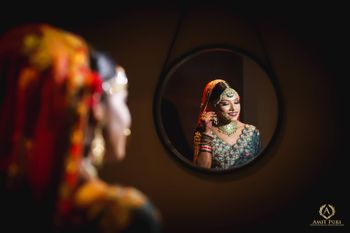 Photo of Bridal getting ready shot in mirror blue lehenga