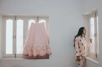 bride in night suit with lehenga on hanger