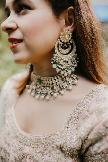 Heavy earrings and choker on a girl in dull pink outfit