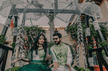 mehendi couple seating idea with lace umbrellas hanging