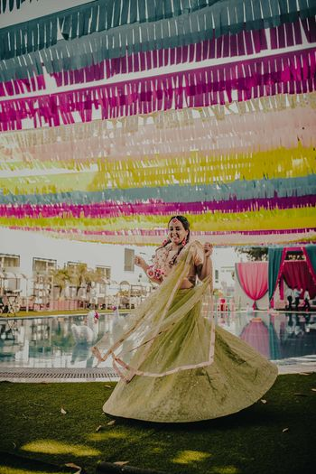 A bride in green twirling on her mehndi day