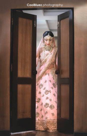 Bride entering through door in light pink and gold lehenga