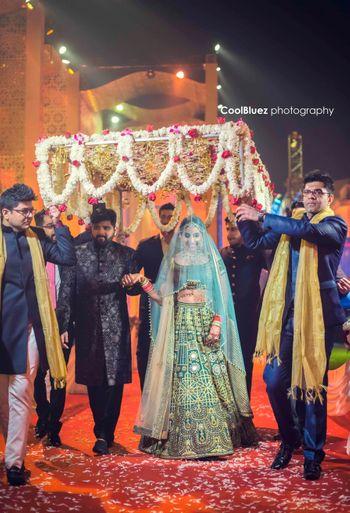 A bride in green enters under a phoolon a chaadar