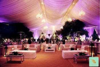 glamorous and elegant reception and engagement theme in white and gold with ceiling drapes and white sofas with hanging chandeliers
