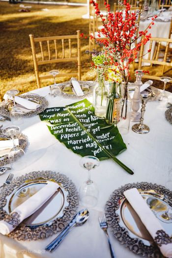 Unique table setting with handwritten note on banana leaf by couple