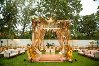 An open mandap with golden drapes