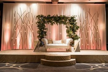 A sleek stage setup with drapes and plant wreath