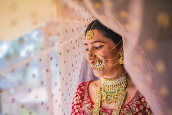 A bride poses for the camera in her red lehenga