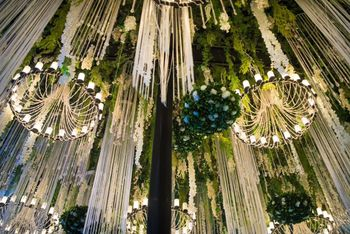 Photo of elegant hanging floral strings and chandeliers reception decor