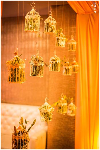 Suspended gold birdcages with foliage