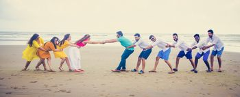 Beach pre wedding shoot with friends tug of war