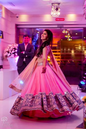Photo of Bride twirling in light pink and blue net lehenga