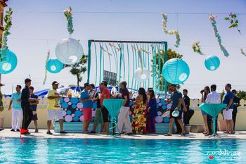 Photo of Blue and white pool party decor with hanging lamps