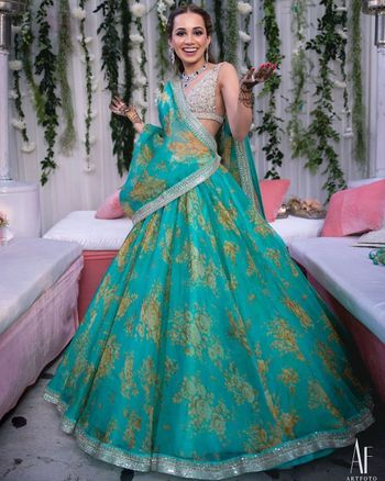 Photo of Bride wearing a printed lehenga with a plunging neck blouse.