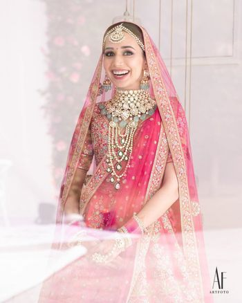 Photo of Bride wearing an elaborate choker with pink lehenga.