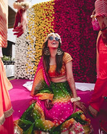 Bride dressed in a bandhani lehenga for her haldi.