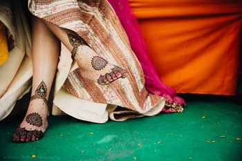 Bride sitting cross legged showing mehendi on feet