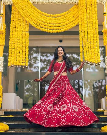 Bride twirling in her red lehenga.