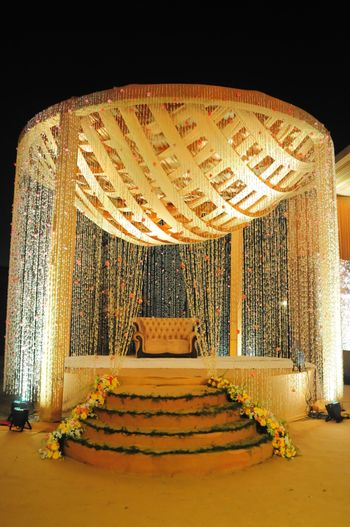 A dome-shaped mandap decorated with floral strings.