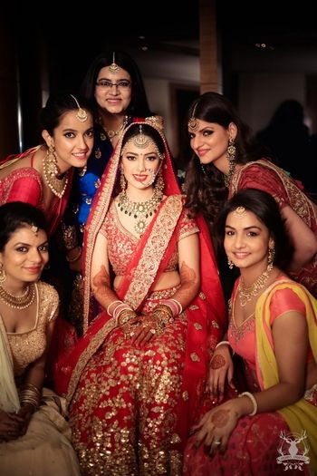 Photo of Bride in red and gold lehenga with bridesmaids