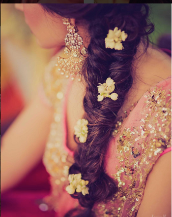 Mehendi hairstyle with side braid and flowers