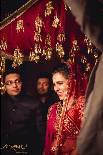 Bride entering under red phoolon ki chadar with kaleere