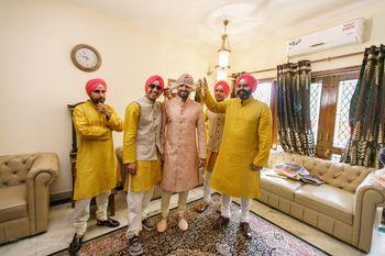 Coordinated groomsmen in yellow kurtas and pink turbans