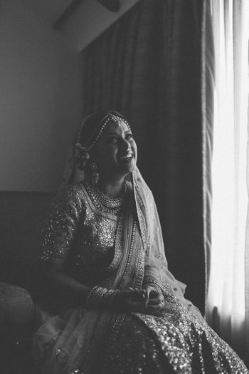 Photo of Black and white bridal candid portrait next to window