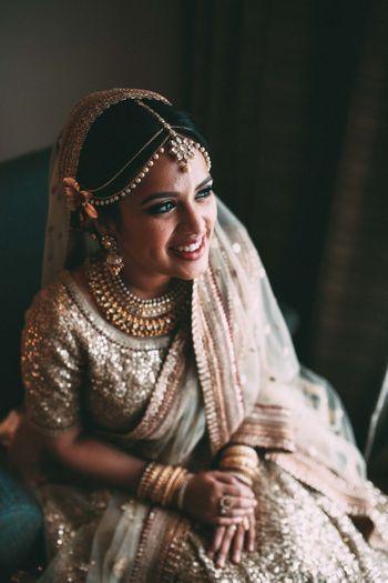 Smiling bride in gold sequin lehenga
