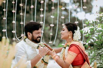 cute south indian couple portrait against floral string backdrop