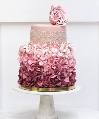 Photo of Two-tier fondant cake frosted with florals.