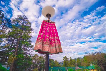 Photo of Bright pink and gold lehenga on lamp post outside