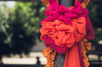 Photo of Pillar covered with cloth bow and floral strings