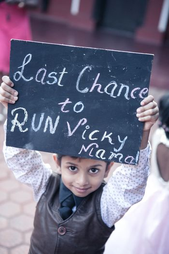 Kid holding placard with cute saying for bridal entry