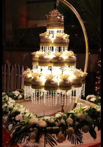 White hanging chandelier cake with smaller cakes
