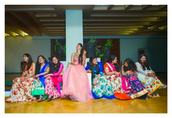Photo of Bride with bridesmaids in coordinated floral lehengas