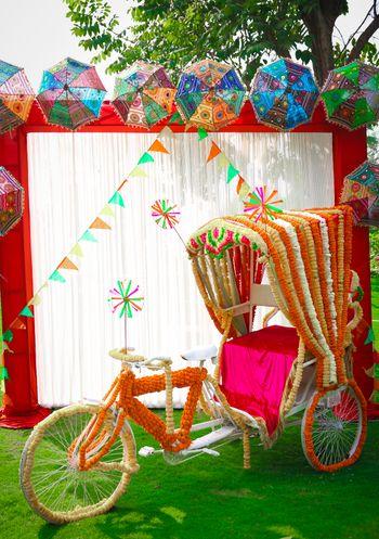 Colourful mehendi photobooth with decorated rikshaw
