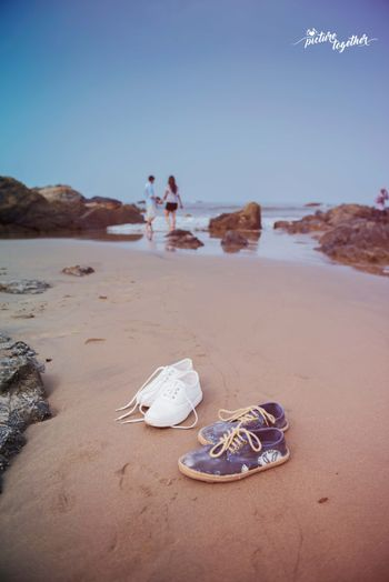 Beach pre wedding shoot with shoes on sand