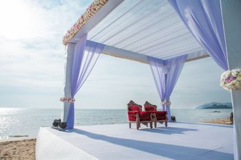 Photo of Mandap on beach with lilac drapes and white flowers