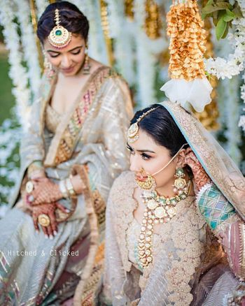 Photo of wedding day bridal portrait with her sister while adjusting jewellery