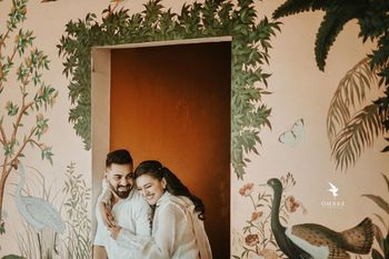 Couple posing against a beautifully hand-painted wall.