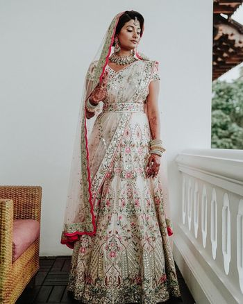 Bride dressed in ivory belted lehenga for her wedding.
