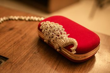 Photo of Red and gold bridal clutch with bejewelled peacock