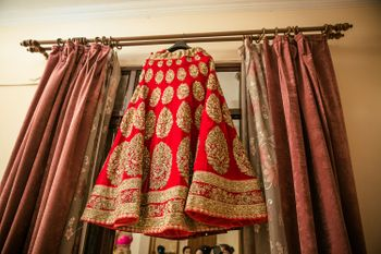 Photo of Red and gold bridal lehenga on hanger on curtain rod